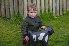 Kleinkind- und Spielzeugkuh lizenzfreie stockbilder