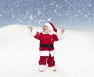 Kleinkind in Weihnachtsmann-Ausstattung, die im Schnee, oben schauend steht Lizenzfreies Stockfoto