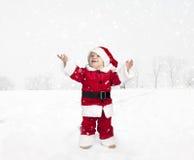 Kleinkind in Weihnachtsmann-Ausstattung, die im Schnee, oben schauend steht Lizenzfreie Stockfotografie