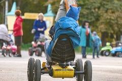 Kleinkind, welches das Minispielzeugauto in der Straße f fährt stockfotos