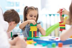 Kleinkinder bauen Blockspielwaren zu Hause oder Kindertagesst?tte auf Emotionale Kinder, die mit Farbbl?cken spielen P?dagogische stockfotografie