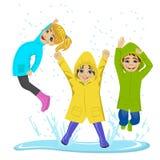 Kleinkinder, die auf der Pfütze trägt bunte Regenmäntel und Stiefel spielen stock abbildung