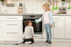 Kleinkinder, die Brötchen im Ofen backen lizenzfreies stockbild