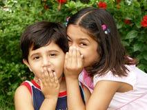 Kleinkinder, die Geheimnisse erklären Stockbilder