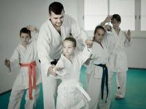 Kleinkinder, die Karatetritte mit männlichem Trainer tun Lizenzfreies Stockbild