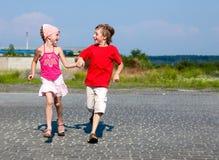 Kleinkinder, die in Straße laufen Stockfotografie