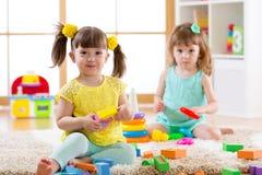 Kleinkinder, die zu Hause mit bunten Spielwaren auf dem Boden oder Kindergarten spielen Lernspiele für Kinder Stockfotografie