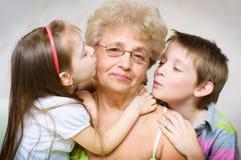 Kleinkinderen die grootmoeder kussen Royalty-vrije Stock Afbeeldingen