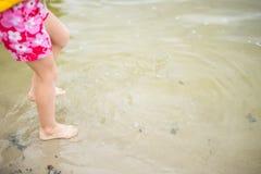 Kleinkindfüße im Wasser am Strand Stockfotos