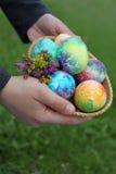 Kleinkindhände, die Ostereier anhalten Lizenzfreie Stockbilder