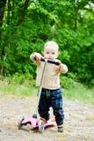 Kleinkindjunge auf dem Roller Lizenzfreie Stockfotos