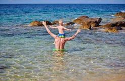 Kleinkindjunge auf den Schultern des Vaters am Strand stockfotos