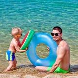 Kleinkindjunge auf Strand mit Vater stockfoto