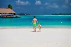 Kleinkindjunge auf Strand mit Vater stockbild
