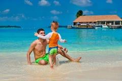 Kleinkindjunge auf Strand mit Vater lizenzfreie stockbilder
