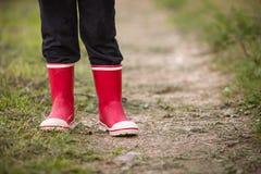 Kleinkindjunge in den Regengummistiefeln Bein ` s Schuss Kind in den hellen roten Schuhen Auf einer Landschaftsstraße draußen Stockbild