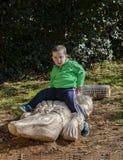 Kleinkindjunge, der auf einer Krokodilstatue sitzt Stockbild