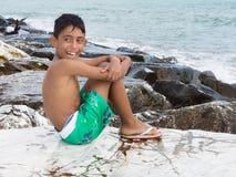 Kleinkindjunge, der auf Felsen sitzt Stockfoto