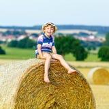 Kleinkindjunge, der auf Heuballen im Sommer sitzt Stockbilder