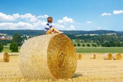Kleinkindjunge, der auf Heuballen im Sommer sitzt Stockfotos