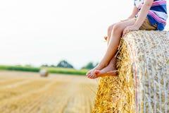 Kleinkindjunge, der auf Heuballen im Sommer sitzt Stockfotografie