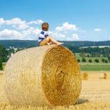 Kleinkindjunge, der auf Heuballen im Sommer sitzt Lizenzfreie Stockbilder