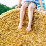 Kleinkindjunge, der auf Heuballen im Sommer sitzt Lizenzfreie Stockfotografie