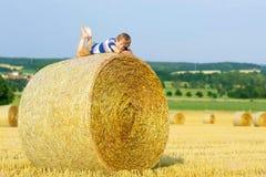 Kleinkindjunge, der auf Heuballen im Sommer sitzt Lizenzfreies Stockbild
