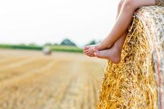 Kleinkindjunge, der auf Heuballen im Sommer sitzt Lizenzfreies Stockfoto