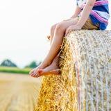Kleinkindjunge, der auf Heuballen im Sommer sitzt Stockfoto