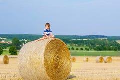 Kleinkindjunge, der auf Heuballen im Sommer sitzt Stockbild