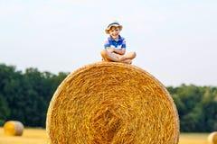 Kleinkindjunge, der auf Heuballen im Sommer sitzt Lizenzfreie Stockfotos
