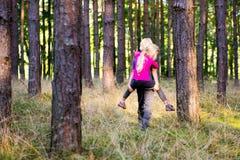 Kleinkindjunge, der draußen seiner Schwester Doppelpol im Wald gibt Stockfotografie