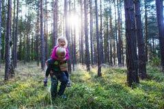 Kleinkindjunge, der draußen seiner Schwester Doppelpol im Wald gibt Lizenzfreie Stockfotografie