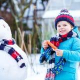 Kleinkindjunge, der einen Schneemann im Winter macht Stockfotografie