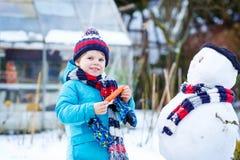 Kleinkindjunge, der einen Schneemann im Winter macht Lizenzfreie Stockfotos