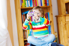 Kleinkindjunge, der Fotos mit photocamera, zuhause macht Stockbild