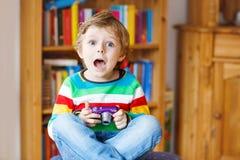 Kleinkindjunge, der Fotos mit photocamera, zuhause macht Stockfotografie