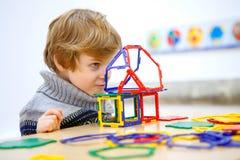 Kleinkindjunge, der geometrische Zahlen mit Plastikblöcken errichtet Stockfoto