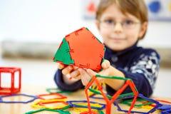 Kleinkindjunge, der geometrische Zahlen mit Plastikblöcken errichtet Stockbild
