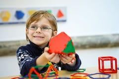 Kleinkindjunge, der geometrische Zahlen mit Plastikblöcken errichtet Lizenzfreie Stockfotografie