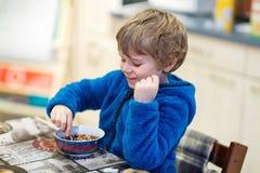 Kleinkindjunge, der Getreide zum Frühstück isst Stockbilder