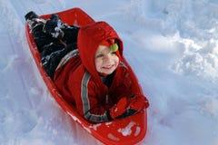 Kleinkindjunge, der im Schnee sledding ist Lizenzfreie Stockfotos