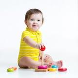 Kleinkindjunge, der mit bunter Spielzeugpyramide spielt Lizenzfreies Stockfoto