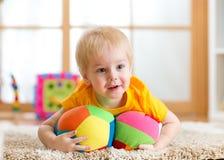 Kleinkindjunge, der mit den Spielwaren Innen spielt Stockbild