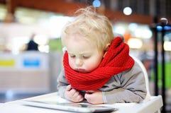 Kleinkindjunge, der mit einer digitalen Tablette spielt Stockbild