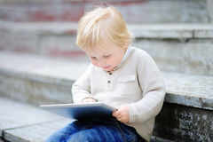 Kleinkindjunge, der mit einer digitalen Tablette spielt Lizenzfreie Stockfotografie