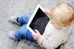 Kleinkindjunge, der mit einer digitalen Tablette spielt Lizenzfreies Stockbild