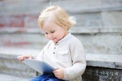 Kleinkindjunge, der mit einer digitalen Tablette spielt Stockbilder