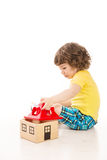 Kleinkindjunge, der mit Holzhaus spielt Stockbild
